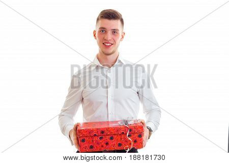 hilarious lovable guy looks straight and holding a gift isolated on white background