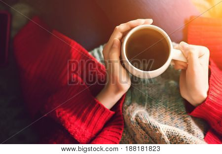 Tea time in the morning. Woman hands holding cup of tea in the morning sunlight. Beautiful girl in sweater with beverage.