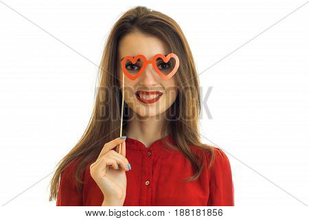 young charming wonderful girl laughs and keeps near eye red paper glasses close-up isolated on white background