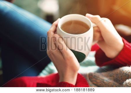 Tea time at morning. Woman hands holding cup of tea in the morning sunlight.