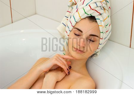 cute young girl with a towel on head lies in the bathtub with closed eyes