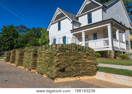 Horizontal photo of green and brown sod on wooden pallets with partial white house and trees in the background
