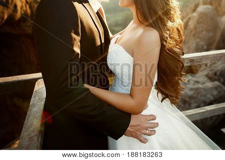 Happy Stylish Bride And Groom Holding Hands And Embracing In Evening Sun Light. Gorgeous Wedding Cou