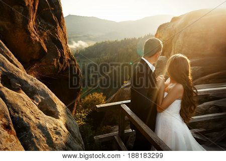Gorgeous Wedding Couple Embracing In Sunlight, Looking At Sun. Happy Stylish Bride And Groom Holding
