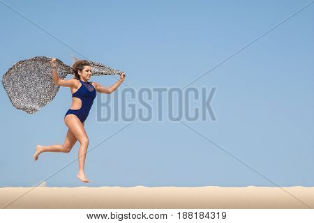 Pretty young brunette with a scarf running in the sand