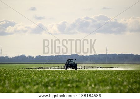 Tractor With A Spray Device For Finely Dispersed Fertilizer. Tractor On The Sunset Background. Tract