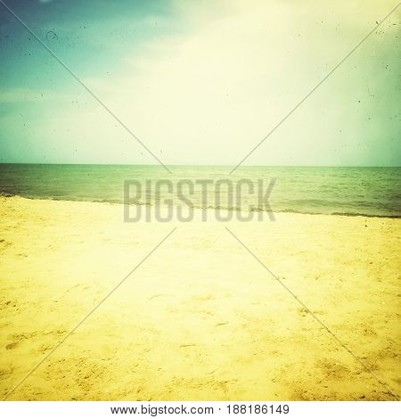 Sea and sand beach. Retro style photo with light effect dust and scratches.