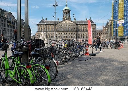 AMSTERDAM NETHERLANDS - MAY 14 2017: Royal Palace in Dam Square and bike parking