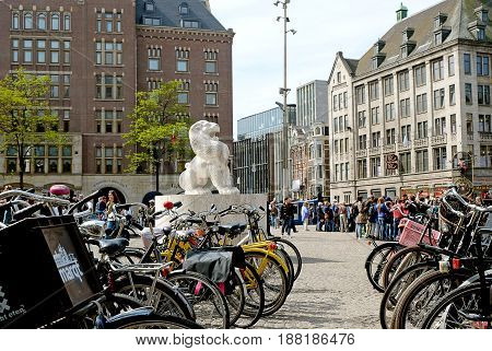 AMSTERDAM NETHERLANDS - MAY 14 2017: Lion in Dam Square and bike parking