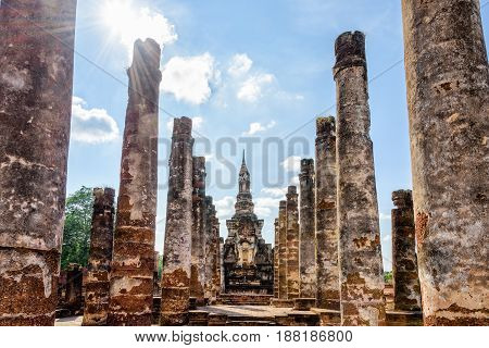Ancient pagoda among the ruins pillars under the bright sun at Wat Maha That temple in Sukhothai Historical Park is an old city and famous landmark of Sukhothai Province Thailand