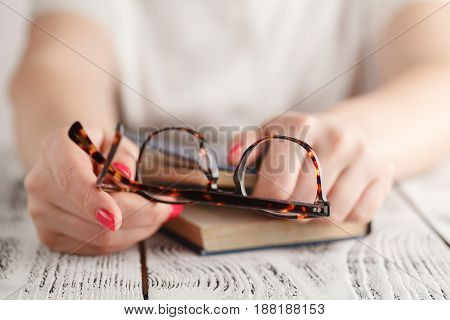 Eyeglasses With Woman Reading Book In Room, Selective Focus