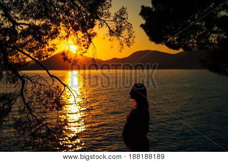 Silhouette of a pregnant woman at sunset by the sea Montenegro