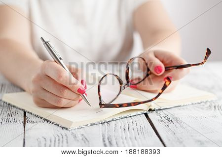 Woman Writing In Notepad Placed On Bright Desktop. Education Concept