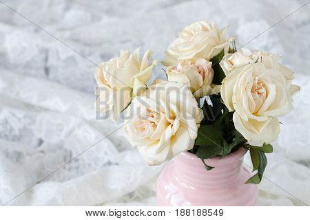 Bouquet of white roses on white lace
