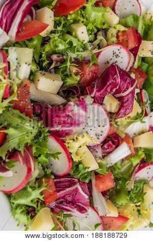 Fresh salad with mixed greens radish cheese and tomato. Italian Mediterranean or Greek cuisine. Vegetarian vegan food. Top view