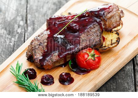 Grilled Ribeye Steak on bone with berry sauce potatoes tomatoes and rosemary on cutting board on wooden background close up. Hot Meat Dishes