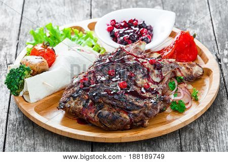 Grilled Ribeye Steak on bone with berry sauce fresh salad and grilled vegetables on cutting board on wooden background close up. Hot Meat Dishes