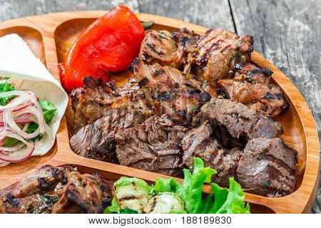 Assorted delicious grilled meat and vegetables with fresh salad and bbq sauce on cutting board on wooden background close up. Hot Meat Dishes. Top view