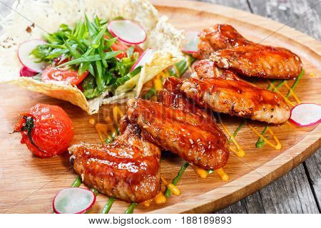 Fried chicken wings with fresh salad grilled vegetables and bbq sauce on cutting board on wooden background close up. Hot Meat Dishes. Top view
