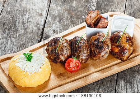 Juicy delicious meat cutlets and hominy or Corn porridge Polenta with goat cheese on cutting board on wooden background close up. Hot Meat Dishes. Top view