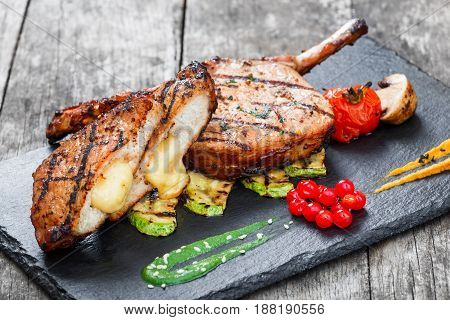 Roasted Pork steak on bone stuffed with cheese grilled vegetables and berries on stone slate background on wooden background close up. Hot Meat Dishes. Top view with copy space