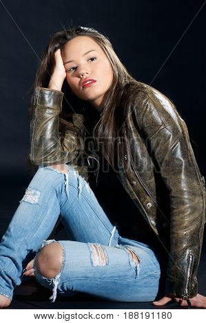 fashion style photo of pensive young beautiful and sexy woman sitting on floor in studio