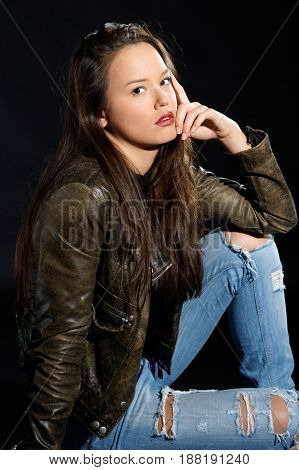 fashion style photo of young beautiful and sexy woman sitting on floor and black background. studio photo