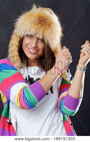portrait of dancing young beautiful smiling brunette woman wering fur hat and colorful clothes and looking in camera