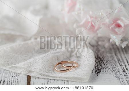 Wedding rings on white satin lace background