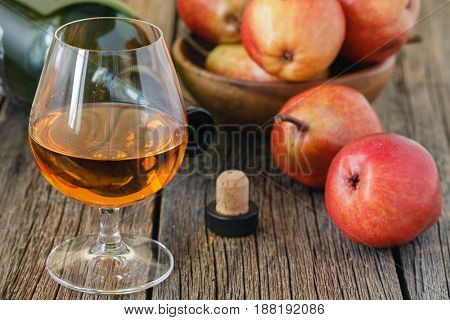 Schnapps with pears and spices on rustic table