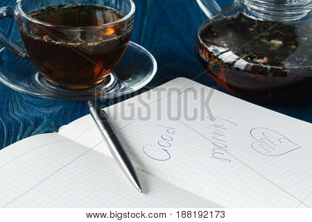 Herbal Tea In A Glass Transparent Cup And Open Pure Notebook