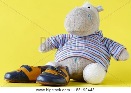 Cute toy shot on yellow with baby shoes