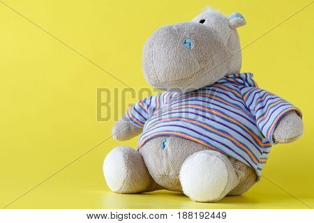 Soft toy Hippo on plain yellow background