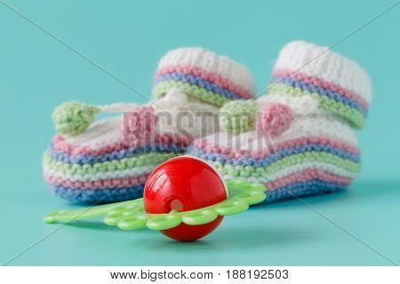 small baby shoes on plain aquamarine background