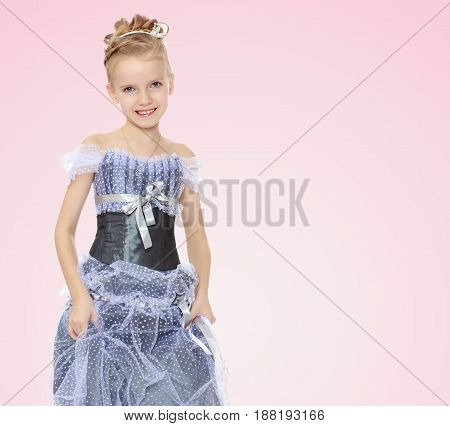 Slender little girl , with beautiful hair on his head, elegant long Princess dress.Girl holding hands to the edge of the dress and put forward a foot to show the shoes.Pale pink gradient background.