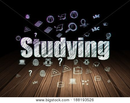 Learning concept: Glowing text Studying,  Hand Drawn Education Icons in grunge dark room with Wooden Floor, black background