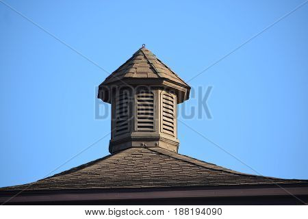a wood and shingle cupola with vents.