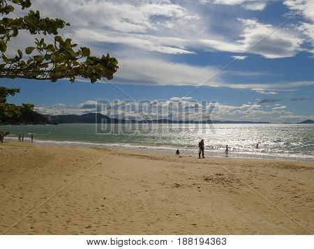 Sunny beach with children playing in the waves of the sea, by the water's edge