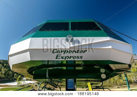 Park City UT May 12 2017: Sun shines of the Carpenter Express lift at the base of the mountain of Deer Valley ski resort. The structure is decoraed with the resort logo.