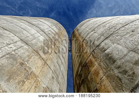 Skyward view of two silos situated close together.