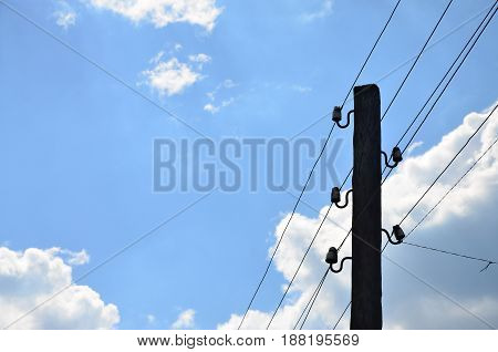 Old Wooden Electric Pole For Transmission Of Wired Electricity On A Background Of A Cloudy Blue Sky.