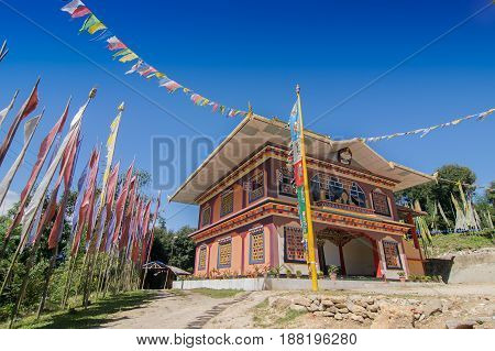 Gurung monastery - a beautiful sunlit Buddhist Monastery at Rinchenpong Sikkim India. Blue clear sky above and Buddhist prayer flags around.