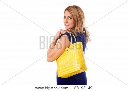 Pretty oman in blue dress with bright wicker tote bag.Isolated on the white studio background