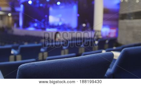Blurred blue chairs in the concert hall against the scene