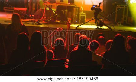 Abstract blurred - young man sitting on a rock concert in front of the stage