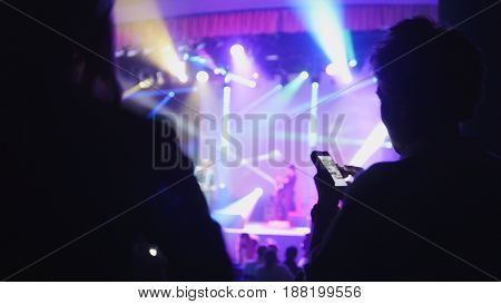Abstract blurred shadows of people in the foreground at the concert in the club