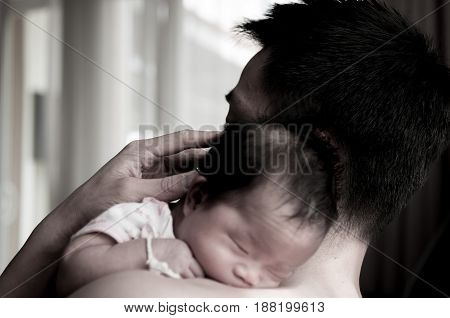 Father holding his newborn baby beside window. After Milk from mother's breast is a natural medicine to baby. Mother day bonding concept with newborn baby nursing.