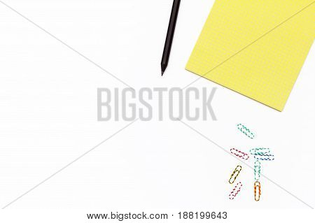 Yellow Notepad, Black Pencil, And Colored Paper Clips On A White Background. Minimal Business Concep
