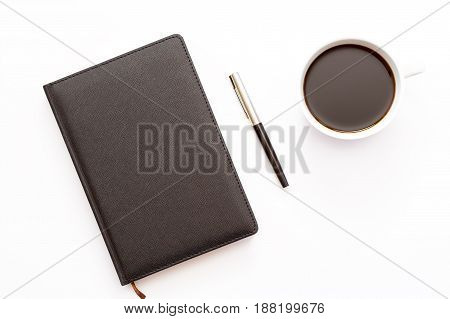 Black Diary, Pen And A Cup Of Black Coffee On A White Background. Minimal Business Concept. Flat Lay