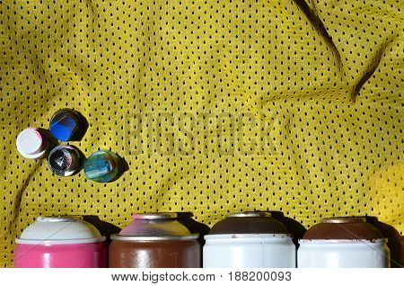 Several Caps For Used Aerosol Paint Sprayers Lie On The Sports Shirt Of A Basketball Player Made Of